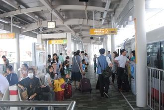 モノレールが停止し、冷房の止まった車内からホームに出て待機する乗客ら=20日午前9時44分、那覇市・美栄橋駅