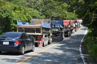 警察車両に前後を守られてN1ゲートを目指す大型トラック=23日午10時40分ごろ、東村安波の県道70号
