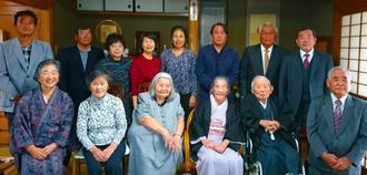 正月で集まった子や孫とともに記念撮影する入嵩西清佐さん(前列右から2人目)、秀さん(同3人目)夫妻=1日、石垣市新川(家族提供)