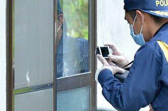米軍のものとみられる銃弾が貫通したガラス戸の写真を撮る県警鑑識職員=2018年6月