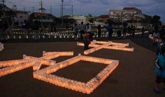 夕闇せまる中「平和」の文字が浮かび上がった=日、沖縄市美里公園