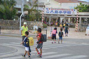 教師や地域住民に見守られながら登校する八島小の児童たち=18日午前8時すぎ、石垣市八島町