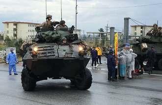 市民の抗議を受けながらキャンプ・シュワブを出る米軍車両=18日午前8時半すぎ、名護市辺野古