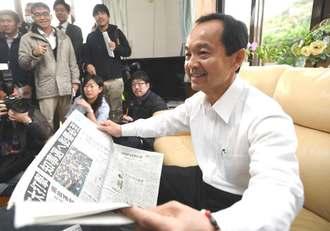 当選から一夜明け、自宅で新聞を広げる渡具知武豊さん=5日午前9時すぎ、名護市許田