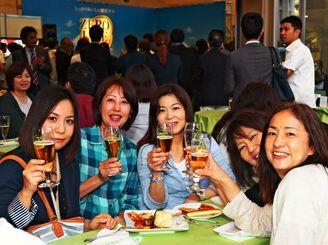 タイムスビル1階に臨時オープンしたオリオンビールのカフェ。「オリオンゼロライフ」で乾杯する女性客ら=2日、那覇市久茂地