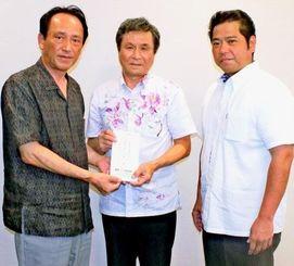 恵和興産の友寄隆文代表(中央)と島袋元・常務(右)=16日、沖縄タイムス社