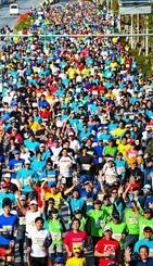 スタートの合図で一斉に駆け出すフルマラソンのランナー=19日午前9時すぎ、沖縄市・県総合運動公園前(喜屋武綾菜撮影)