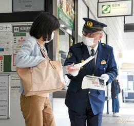 JR湯河原駅でチラシを配り情報提供を呼び掛ける、神奈川県警小田原署の野崎剛志署長(右)=21日午前、神奈川県湯河原町