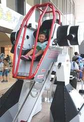 搭乗型ロボット「イケドム」に乗り込み、うれしそうな子ども=10日午前、那覇市・沖縄タイムス社