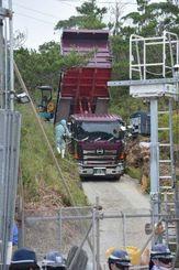 N1地区出入り口ではトラックから砂利を下ろし、道を整備する作業が進められた=26日午前10時すぎ、東村高江