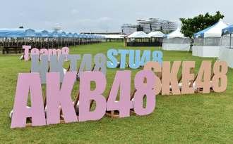 「AKB48」などカラフルな看板が設置された会場=16日午後、豊見城市の豊崎海浜公園