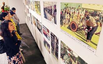 首里城が復元されるまでを記録した写真に見入る来場者=25日、那覇市・タイムスギャラリー