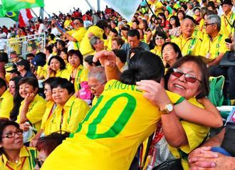 閉会式会場で、お互いの顔を見つけて寄り抱き合う参加者ら=30日午後、セルラースタジアム