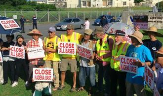 VFPメンバーと共にゲート前で「We shall overcome(勝利の日まで)」を合唱する参加者=2日午前、沖縄市山内・嘉手納基地第5ゲート