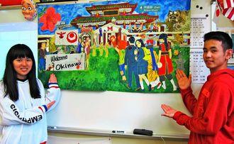 ミルトン高日本語クラスで、用意された歓迎の幕の前に立つ北山高の金城咲良さん(左)と宮里政翔さん