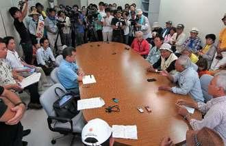県の職員(左)に対し、聴聞期日の延期を認めないよう求める市民ら=6日午後、沖縄県庁