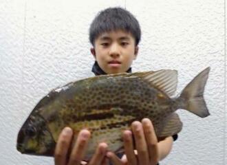 恩納村海岸で37.3センチ1.12キロのカーエーを釣った東江唯斗さん=16日