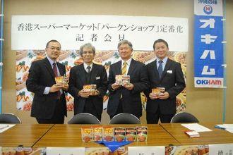 香港の現地スーパーでレトルト2商品の定番化が決まった沖縄ハム総合食品の長濱徳勝社長(右から2人目)=8日、県庁