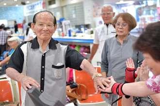 ストライクを取り仲間とタッチする103歳ボウラーの前原信光さん=17日、北谷町桑江・北谷ボウル(下地広也撮影)