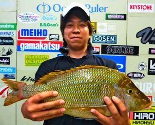 宜野湾浄水場で1.98キロのタマンを釣った安里幸太さん=22日