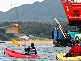 市民らが抗議する中、新たに海中に投入される大型コンクリートブロック(左奥)=5日正午ごろ、名護市・大浦湾上