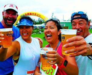 走り終えて乾杯する(左から)クリスティーナさんの夫のトムさん、クリスティーナさん、アンジェラさん、夫のダンさん=23日、久米島町営仲里野球場