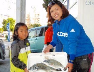 なうら橋で40・5センチ、1・02キロのミナミクロダイを釣った譜久村真美さん(右)=14日