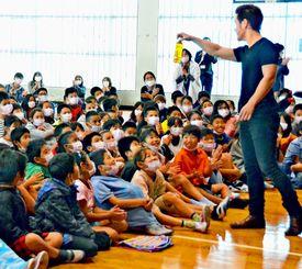 MASAさん(右)のマジックに驚く大謝名小学校の児童ら=12日、宜野湾市の大謝名小学校