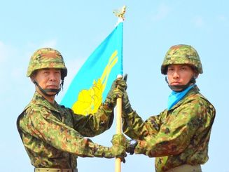 西部方面隊の小川総監(左)から隊旗を受け取る与那国沿岸監視隊の塩満隊長=28日、沖縄県与那国町