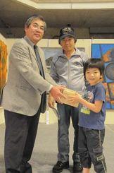 沖縄タイムスの上原徹文化事業局長から記念品のシーサーを受け取る下地湊君(右)と祖父の徹さん