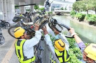 久茂地川に投棄された自転車を撤去する作業員=6月19日、那覇市・沖縄都市モノレール県庁前駅下