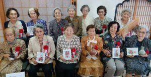 安元文子さん(後列右から2人目)作の陶器や上原米子さん(同5人目)の絵を贈られ、笑顔を見せる三高女21期生たち=那覇市牧志・ホテル山の内