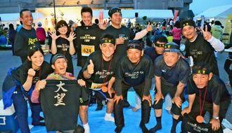 11人で出場した久高秀樹社長(前列左から3人目)ら=今帰仁村総合運動公園