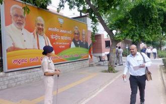 下院選の開票が進む中、与党インド人民党の事務所前を警備する治安当局者=23日、ニューデリー(共同)