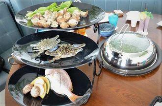 「蒸気海鮮」専用の蒸気鍋(中央)と県産食材=30日、北谷町美浜