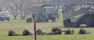 離島奪回訓練のデモンストレーションで、地面に伏せ銃撃体制をとる水陸機動団。後方右に見えるのは水陸両用車=7日、長崎県佐世保市の相浦駐屯地