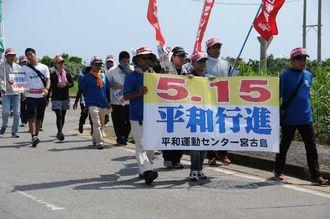「陸自配備反対」「新基地建設阻止」などを訴えながら行進する参加者=9日、宮古島市平良下里