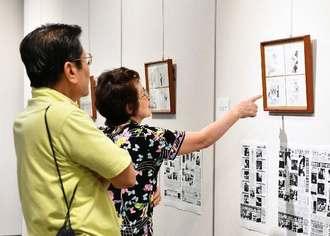 砂川さんの「時事漫評」の原画に見入る来場者=27日午前、那覇市久茂地・タイムズギャラリー