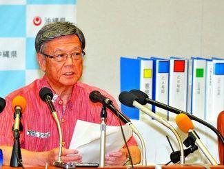 国交相への意見書提出について会見する翁長雄志知事。後ろは提出した意見書や弁明書など関連資料=21日午後、沖縄県庁