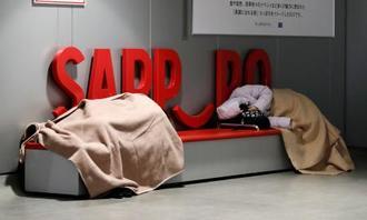 開放された「札幌駅前通地下歩行空間」で、毛布にくるまり仮眠する人たち=22日午前2時48分