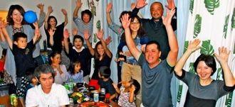 プロ入りが決まり、万歳で喜ぶ福地投手の(右から)母幸子さん、父安夫さんら家族=23日、名護市大北の実家