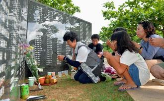 家族で線香を上げ冥福を祈る遺族ら=23日午前9時すぎ、糸満市摩文仁・平和の礎
