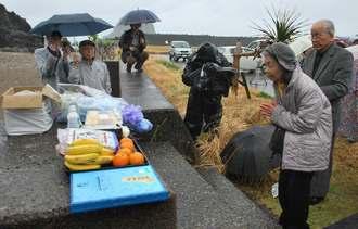 5人の遺体が埋葬された海岸で、犠牲者を悼み、手を合わせる遺族ら=18日、奄美大島大和村の今里漁港