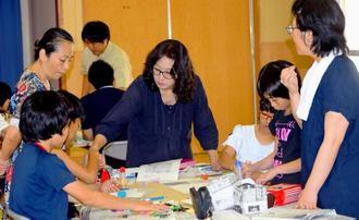 活発な意見を出しながら記事を貼り付ける親子ら=16日、宜野湾市・嘉数小学校