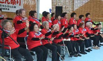 振り付きでCDデビュー曲を披露する小浜島ばあちゃん合唱団の女性たち=竹富町小浜、ちゅらさん広場