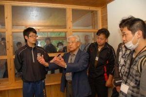 ガラスで仕切られた面会室で当時の様子を説明する平良仁雄さん(前列左から2人目)=名護市済井出・沖縄愛楽園