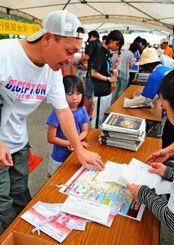 「尚巴志ハーフマラソン」のゼッケンを受け取る選手たち=1日、南城市佐敷のシュガーホール前駐車場