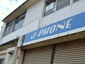 携帯電話の歴史を感じさせる「J―PHONE」の看板=沖縄市住吉