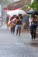 沖縄で梅雨入りし、強い雨の中を小走りで雨宿りできる場所を目指す人たち=5日午前10時20分、那覇市・国際通り(伊藤桃子撮影)