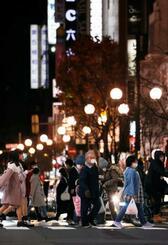 札幌市の繁華街・ススキノを歩く人たち=27日夜